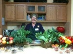 Sequoia Cheney in the kitchen with an abundance of fresh raw fruits and vegetables